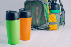 Thermos mugs in front of the backpack Royalty Free Stock Images