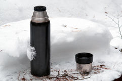 Thermos with open cup on the snow Stock Images