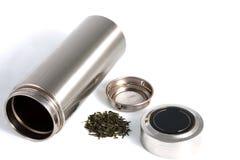 Thermos personnel chinois avec des feuilles de thé vert d'isolement sur le blanc Photo stock