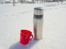 Thermos in the snow. Coffee themos and mug in the snow Stock Photos