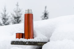 Thermos in the snow. Need to warm up during the winter Stock Photo