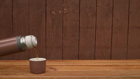 Thermos with tea on wooden background stock video