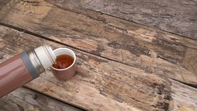 Thermos with tea on wooden board stock video footage