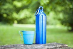 Thermosflasche des blauen Wassers in der Natur auf Holztisch lizenzfreie stockfotografie