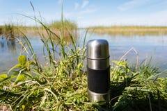 Thermosflasche mit Kaffee oder Tee auf einem Gras Stockfotografie