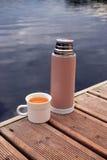 Thermosflasche mit Schale auf Pier Lizenzfreie Stockbilder
