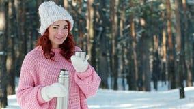 Thermosflaschen in den Händen schließen oben, Hand in gestrickten Handschuhen gießt Tee in eine Schale, Frau gießt heißes Getränk stock footage