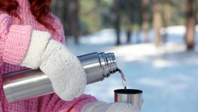 Thermosflaschen in den Händen schließen oben, Hand gießt Tee in eine Schale, Frau gießt heißes Getränk von einer jungen Frau der  stock video