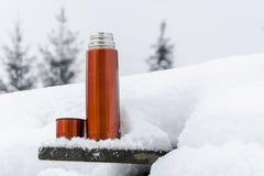 Thermosflessen in de sneeuw stock foto