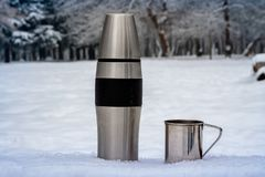 Thermosflessen en kop in de winter in openlucht Wandeling stock foto
