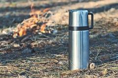 Thermosflessenfles met koffie of thee openlucht Stock Afbeeldingen
