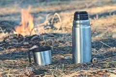 Thermosflessenfles met koffie of thee openlucht Stock Afbeelding