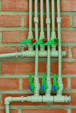 Thermostat. Central heating pipes on the brick wall Stock Image