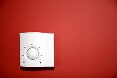 Thermostat. The thermoregulator on red wall stock photo