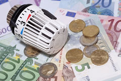 Thermostat with euro coins and banknotes. Stock Images