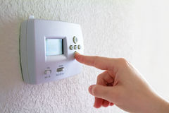 Thermostat and human hand Stock Photo
