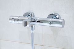 Thermostatic shower faucet. A new modern Thermostatic shower faucet on the wall in bathroom Stock Photos