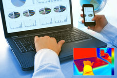 Thermovision image showing heat in the office. Infrared thermography image showing the heat and radiation of Notebook and smartphones in the office Stock Photo