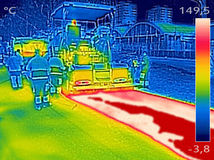 Thermovision image Workers on Asphalting Road street. Infrared thermovision image showing Workers on Asphalting paver machine during Road street repairing works Royalty Free Stock Images