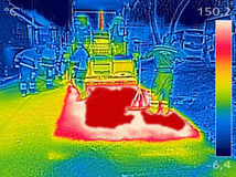 Thermovision image Workers on Asphalting Road street. Infrared thermovision image showing Workers on Asphalting paver machine during Road street repairing works Royalty Free Stock Photo
