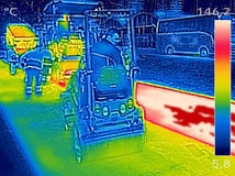Thermovision image Workers on Asphalting Road street. Infrared thermovision image showing Workers on Asphalting paver machine during Road street repairing works Stock Photos