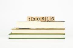 Thesiswoord op houten zegels en boeken Royalty-vrije Stock Foto's