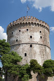 Thessaloniki, Greece. The White Tower with Greek flag waving on top. The White Tower is the landmark of Thessaloniki stock photography