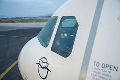 THESSALONIKI GREKLAND - OKTOBER 15, 2016: Ett flygplan på logiporten av flygplatsen, jetway och cockpiten med piloten Arkivbild