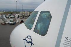 THESSALONIKI GREKLAND - OKTOBER 15, 2016: Ett flygplan på logiporten av flygplatsen, jetway och cockpiten med piloten Royaltyfri Fotografi