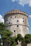 Thessaloniki, Griekenland De Witte Toren met Griekse vlag die op bovenkant golven Stock Fotografie