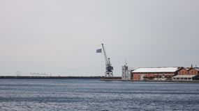 Thessaloniki zeehaven met Griekse vlag stock afbeeldingen