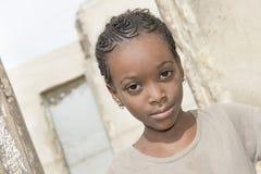 """Thiaroye,塞内加尔,非洲†""""2014年7月30日:站立在她的房子的门的未认出的女孩 免版税库存照片"""