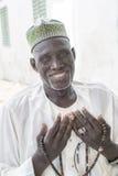 Thiaroye, †«18-ое июля 2014 Сенегала, Африки: Неопознанный мусульманский человек сидя перед грандиозной мечетью Стоковое Изображение RF