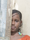 Thiaroye, Senegal, Africa � July 30, 2014: Unidentified girl partially hiding behind a door Royalty Free Stock Photography