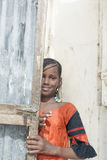 Thiaroye, Senegal, Africa – July 30, 2014: Unidentified girl partially hiding behind a door Stock Photography