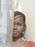 """Thiaroye, Senegal, Afrika †""""30 Juli, 2014: Niet geïdentificeerd meisje die gedeeltelijk achter een deur verbergen Royalty-vrije Stock Fotografie"""