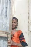 """Thiaroye, Senegal, Afrika †""""30 Juli, 2014: Niet geïdentificeerd meisje die gedeeltelijk achter een deur verbergen Stock Fotografie"""