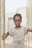 """Thiaroye, Senegal, Afrika †""""30 Juli, 2014: Niet geïdentificeerd meisje die zich bij de deur van haar huis bevinden Royalty-vrije Stock Fotografie"""