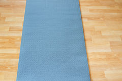 Thick anti slip blue fitness yoga practice or meditation mat on Stock Image