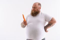 Thick bearded guy making choice of eating Stock Photos