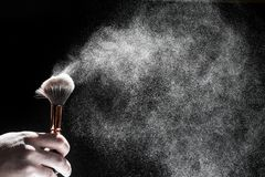 Thick black brush in motion and loose powder particles scattered around. Image stock photo