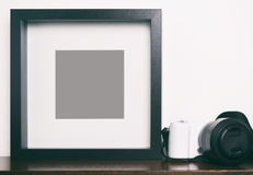 Thick blank black photo frame on shelf with camera royalty free stock photos