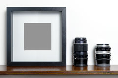 Thick blank black photo frame on shelf camera lens. stock photography