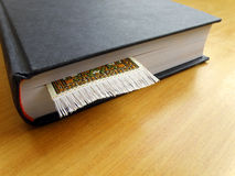Thick book with book mark. An image of a thick hardcover book placed on a wood table, with a bookmark in the book. Simple composition with copy space. Nobody in Royalty Free Stock Images