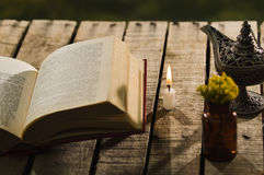 Thick book lying open on wooden surface next to small brown bottle with yellow flowers and Aladin style lamp, beautiful Stock Photos