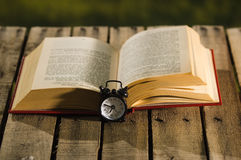 Thick book lying open on wooden surface, old fashioned night table clock sitting next to it, magic concept shoot Royalty Free Stock Photos