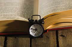 Thick book lying open on wooden surface, old fashioned night table clock sitting next to it, magic concept shoot Royalty Free Stock Images