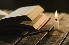 Thick book lying open on wooden surface, wax candle sitting next to it, beautiful night light setting, magic concept Stock Images