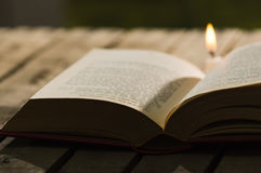 Thick book lying open on wooden surface, wax candle sitting next to it, beautiful night light setting, magic concept Stock Photography