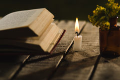 Thick book lying open on wooden surface, wax candle and small bottle with yellow flowers sitting next to it, beautiful Royalty Free Stock Photography
